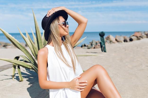 Garota loira e bonita com cabelo comprido está sentada na praia perto de cacto no fundo. ela está segurando um chapéu e olhando para longe. Foto gratuita