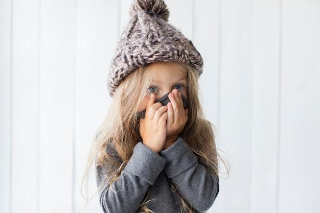 Garota loira engraçada, cobrindo o rosto Foto gratuita