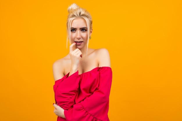 Garota loira excitada sexy em um vestido vermelho em um espaço amarelo do estúdio Foto Premium