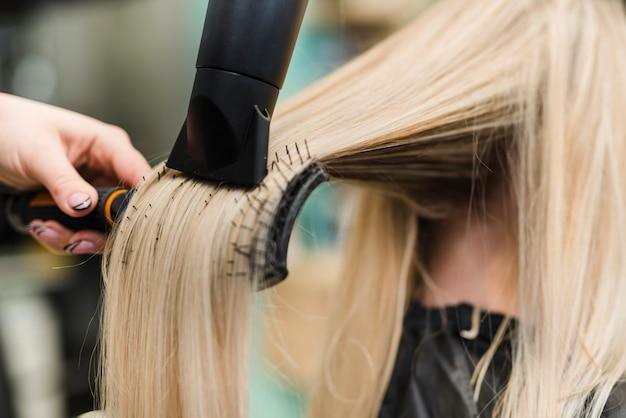 Garota loira fazendo o cabelo dela Foto Premium