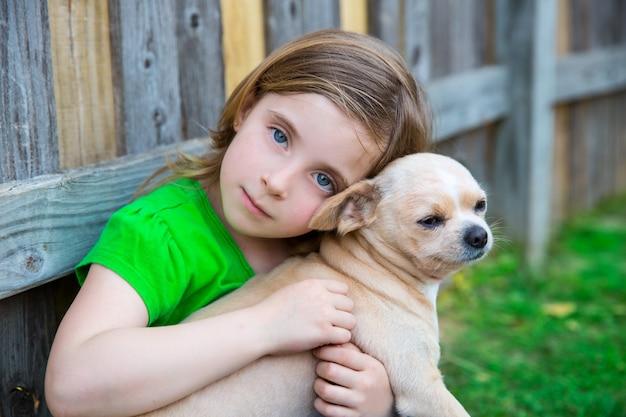 Garota loira feliz com seu retrato cachorrinho chihuahua Foto Premium