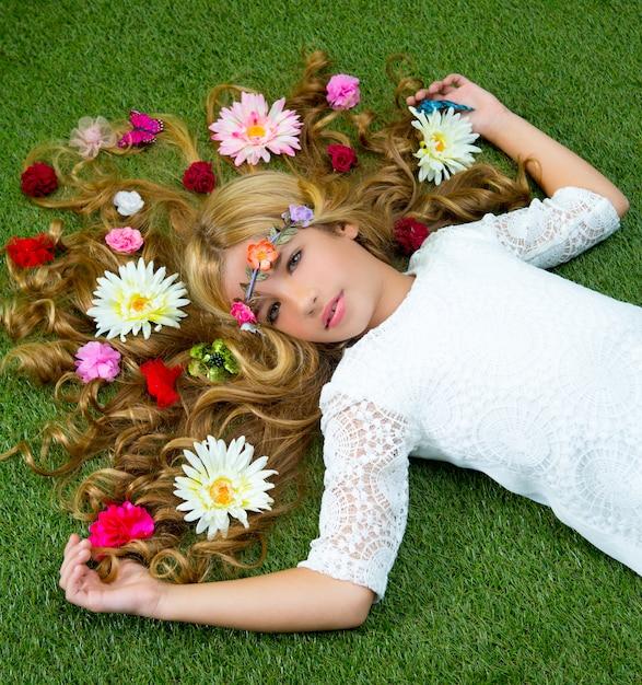 Garota loira primavera com flores no cabelo sobre grama Foto Premium