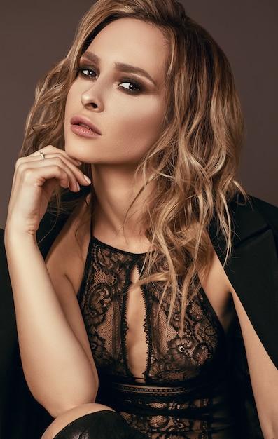 Garota loira sedutora sexy em roupas íntimas e casaco preto Foto Premium