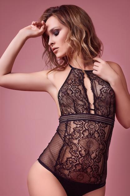 Garota loira sedutora sexy em roupas íntimas em fundo rosa brilhante Foto Premium