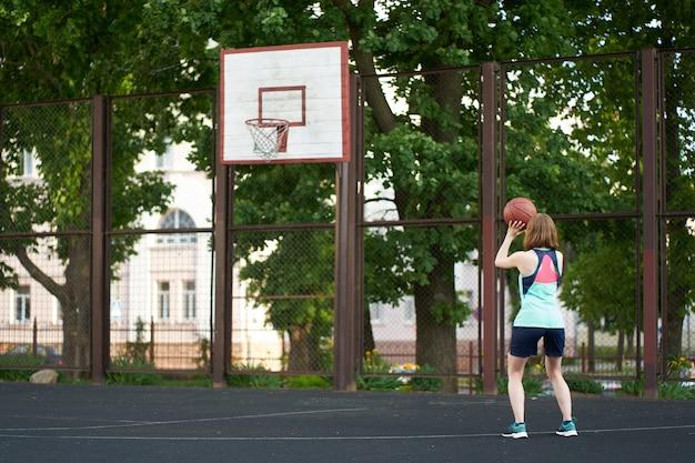 Garota magra ruiva jogando uma bola na cesta de basquete ao ar livre Foto Premium