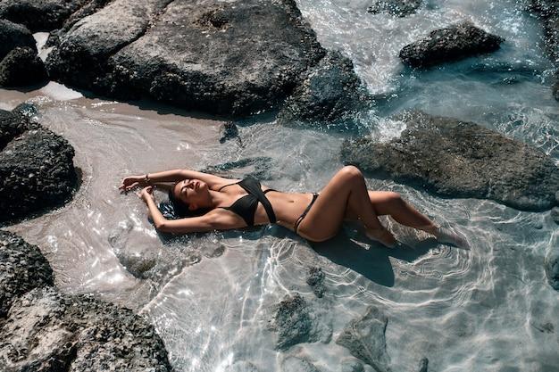 Garota magro atraente em um maiô preto relaxa perto do mar Foto Premium