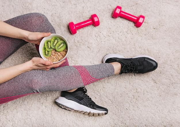 Garota mantém um prato com muesli e kiwi após treino de fitness com halteres Foto gratuita