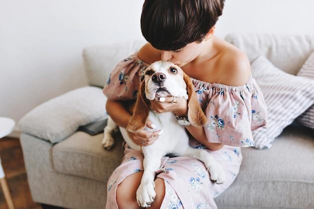 Garota maravilhosa com penteado curto da moda beijando cachorro beagle sentado no sofá cinza Foto gratuita