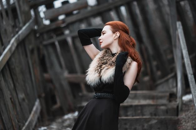Garota marcante com longos cabelos vermelhos em roupas pretas. mulher de vestido preto e peles no pescoço, com luvas pretas longas posando na natureza de inverno. Foto Premium
