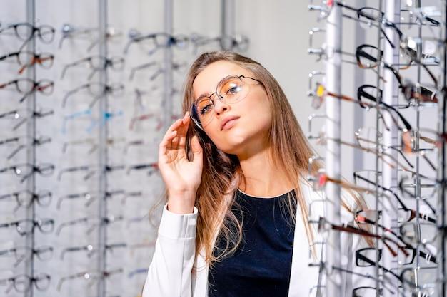 Garota modelo está de pé com um conjunto de óculos na loja ótica Foto Premium