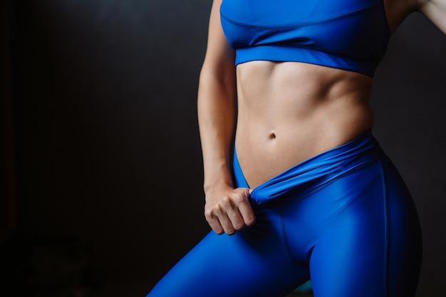 Garota mostra sua barriga bombeada. corpo atlético após dieta e exercícios pesados, cintura fina Foto gratuita