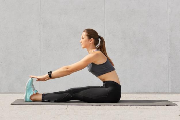 Garota motivada faz exercícios de alongamento ou acrobacias no tapete de fitness, recebe aula de ioga, tem cabelo escuro penteado na cauda de pônei Foto gratuita