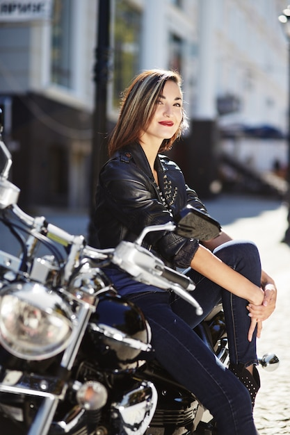 Garota motociclista em uma jaqueta de couro em uma motocicleta Foto gratuita
