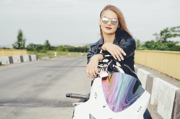 Garota motociclista em uma roupa de couro em uma motocicleta Foto gratuita