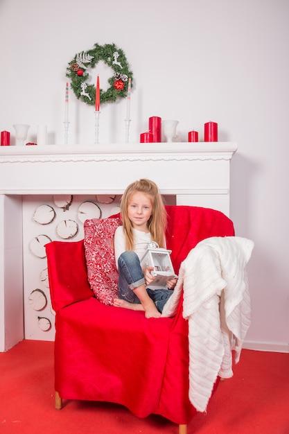 Garota muito sorridente segurando a lanterna de férias, casa é decorada antes da festa de natal. feliz natal decoração na sala de estar. ano novo. imagem vertical Foto Premium
