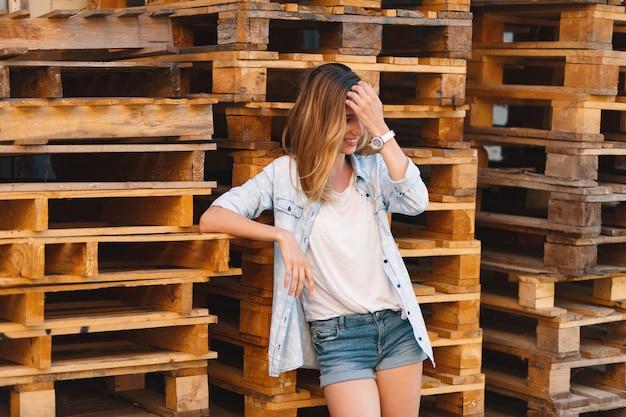 Garota muito sorridente, vestindo jeans, shorts e camisa posando em fundo madeira Foto gratuita