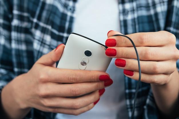 Garota na camisa xadrez, segurando um telefone inteligente nas mãos com manicure vermelho e conecta fones de ouvido Foto Premium