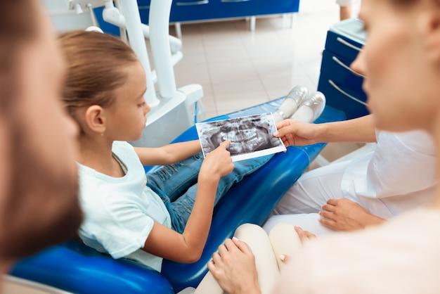 Garota na clínica odontológica. raio x da maxila da mostra do dentista. Foto Premium