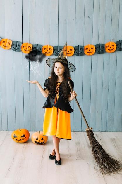 Garota na fantasia de bruxa com conjure vassoura Foto gratuita