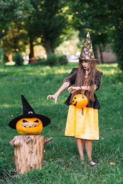 Garota na fantasia de bruxa mostrando chegar às mãos na abóbora Foto gratuita