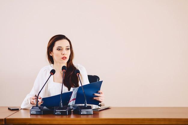Garota na mesa fala em microfones na sala de conferências Foto Premium