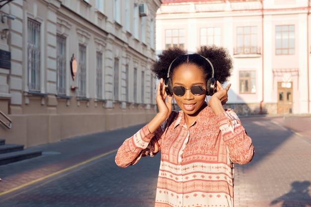 Garota negra afro-americana tem um passeio na cidade à noite e ouvindo música em fones de ouvido. garota de óculos de sol no verão sorri e olhando no pôr do sol. Foto Premium
