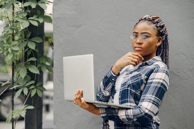 Garota negra em uma cidade de verão com laptop Foto gratuita