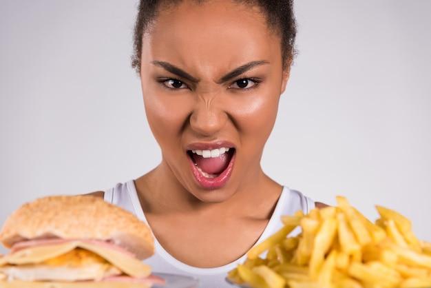 Garota negra, gritando com hambúrguer e batatas fritas. Foto Premium