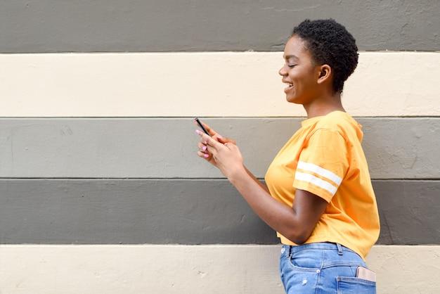 Garota negra, sorrindo e usando seu telefone inteligente ao ar livre. Foto Premium