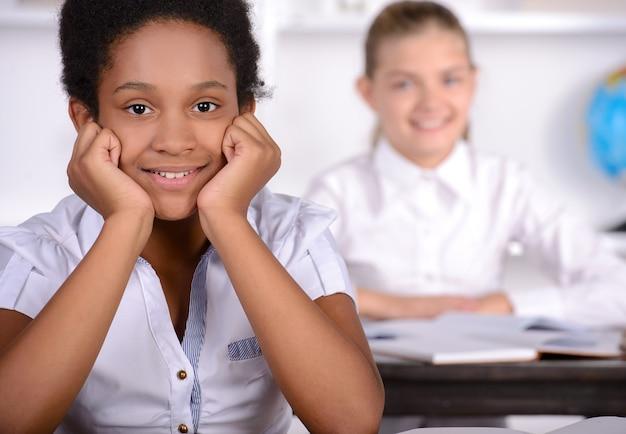 Garota negra sorrindo em classe na escola. Foto Premium