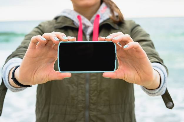 Garota no casaco verde mostra uma tela de telefone em branco sobre um fundo do mar Foto Premium