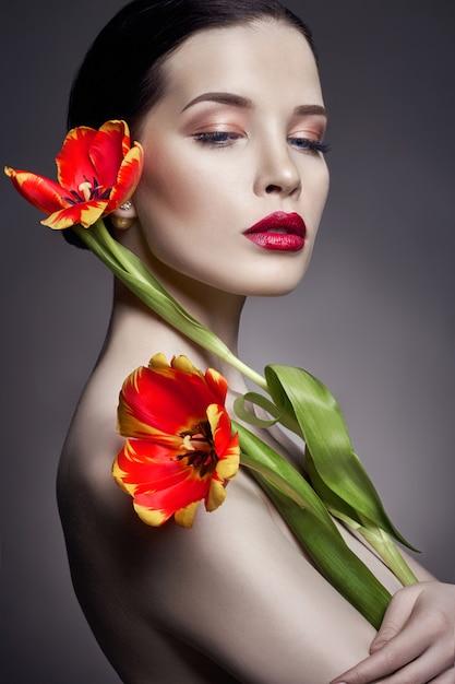 Garota nua nua com flores tulipas na mão e pele perfeita, mulher morena nua sexy. cuidados com a pele do rosto e mãos no verão. maquiagem natural brilhante Foto Premium