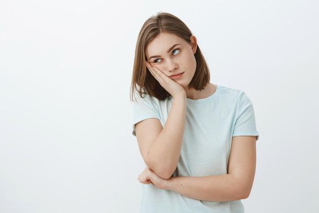 Garota odeia assistir a aulas chatas na universidade, rosto inclinado na mão, revirando os olhos de tédio e aborrecimento em pé indiferente e descontente sobre uma parede cinza em uma camiseta da moda Foto gratuita