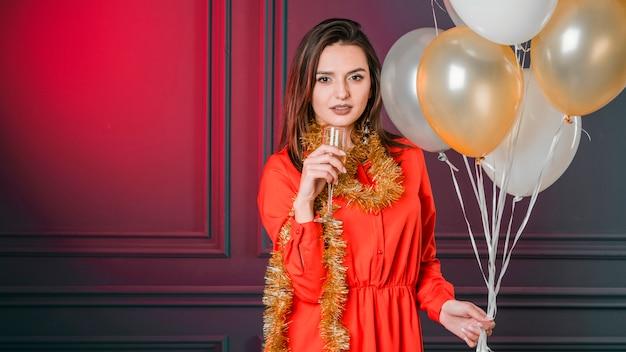 Garota oferecendo champanhe com balões Foto gratuita