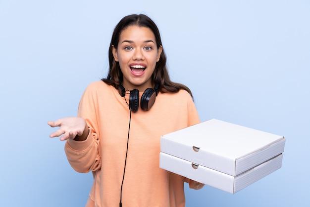 Garota pegando caixas de pizza sobre parede isolada Foto Premium