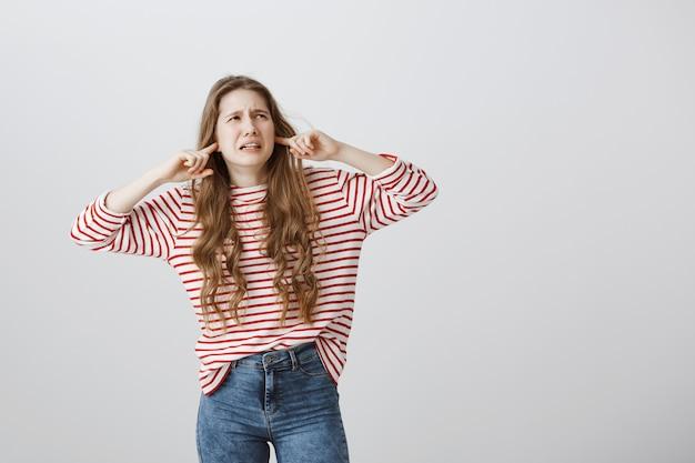 Garota perturbada e irritada fechou os ouvidos e olhou no canto superior direito, reclamando dos vizinhos Foto gratuita