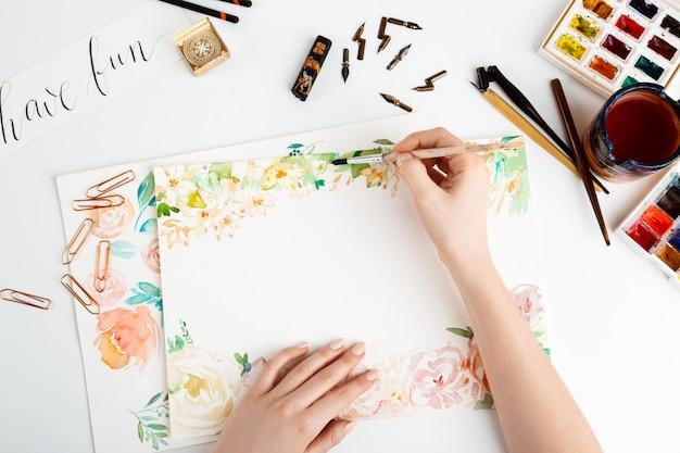 Garota pintando flores em papel com aquarela. Foto gratuita