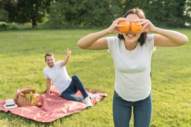 Garota posando com duas laranjas Foto gratuita