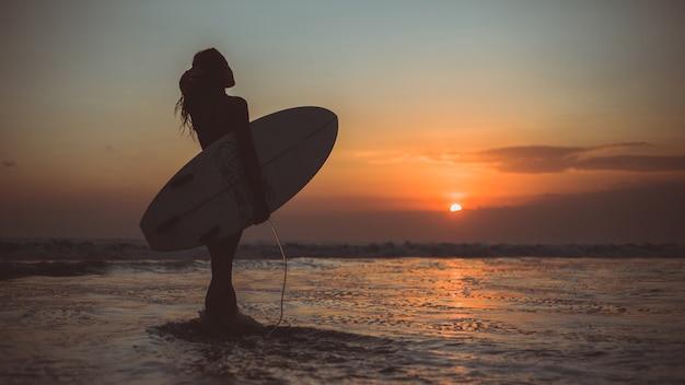 Garota posando com uma placa ao pôr do sol Foto gratuita