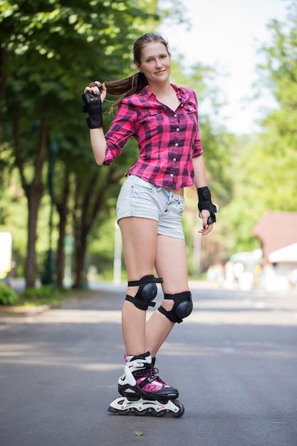 Garota posando no parque com suas lâminas na Foto gratuita