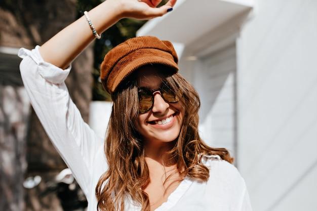 Garota positiva em óculos escuros e boné de veludo levantou a mão e sorrindo contra edifícios. Foto gratuita