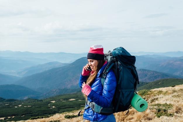 Garota positiva falando ao telefone durante uma caminhada pelo grand canyon usando boas comunicações móveis, Foto Premium