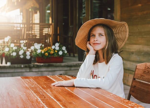 Garota pré-adolescente atraente no chapéu de palha com olhos azuis, sentado e sonhando na mesa no quintal da casa de madeira Foto Premium