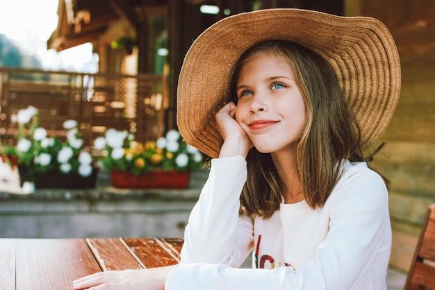 Garota pré-adolescente atraente no chapéu de palha com olhos azuis, sentado e sonhando na mesa Foto Premium