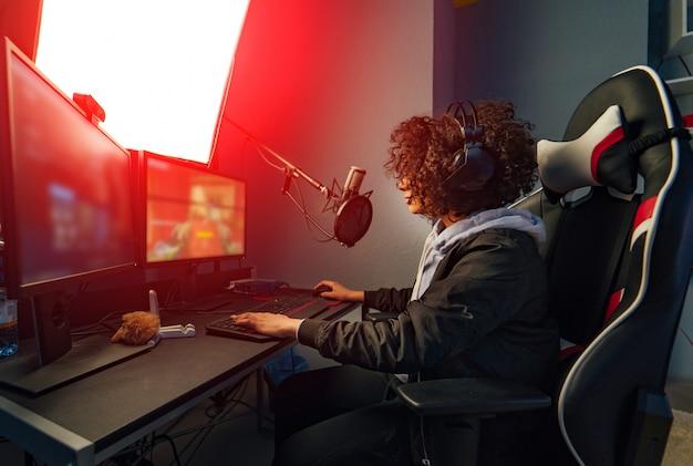 Garota profissional jogador joga videogame no computador dela. ela está participando do torneio de jogos cibernéticos on-line, joga em casa ou no cibercafé. ela usa fone de ouvido para jogos Foto Premium