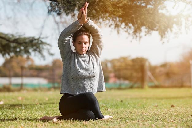 Garota relaxada praticando ioga ao ar livre Foto gratuita
