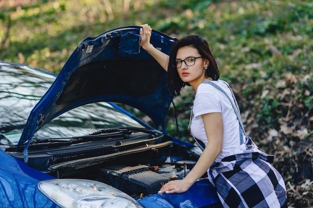 Garota repara o carro com um capô aberto na estrada Foto Premium