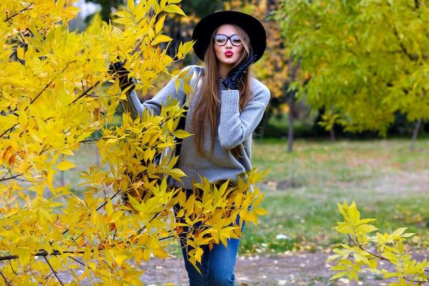 Garota romântica de cabelos compridos posando com expressão facial de beijo enquanto caminhava no parque outono. retrato ao ar livre do jovem europeu elegante em jeans e chapéu ao lado do arbusto amarelo. Foto gratuita