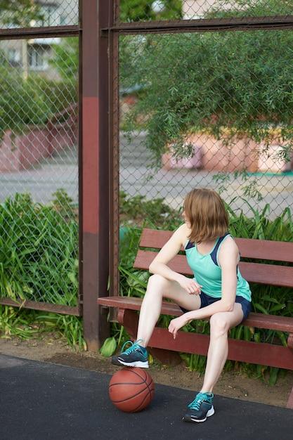 Garota ruiva caucasiana magra com bola no chão sentado e esperando um jogo na quadra de basquete ao ar livre Foto Premium