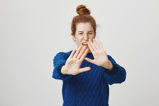 Garota ruiva descontente dizendo não, mostre a placa de pare, cubra o rosto com as mãos estendidas Foto gratuita